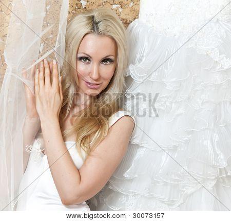 The happy bride tries on a wedding dress