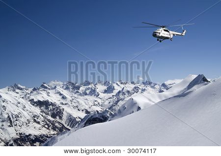 Helicopter in snowy mountains. The sunny day poster