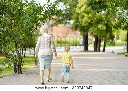 Beautiful Granny And Her Little Grandchild Walking Together In Park. Grandma And Grandson