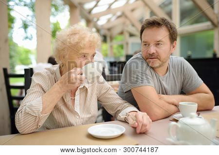 Beautiful Senior Lady With His Mature Son Drinking Tea In Outdoors Cafe Or Restaurant. Elderly Lady