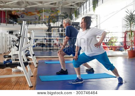 Active Couple Of Seniors Exercising At Gym. Sportive Happy Elderly Woman Performing Exercise In A Fi