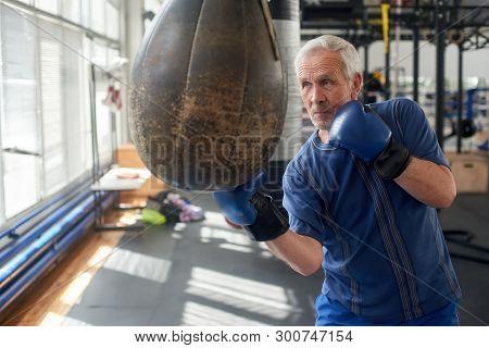 Elderly Man Hitting Punching Bag In Boxing Studio. Senior Caucasian Man In Gloves Beats Punching Bag