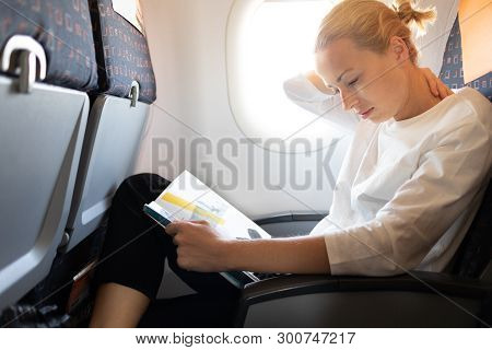 Woman Feeling Neck Pain While Reading In Flight Magazine On Long Intercontinental Airplane Flight. F