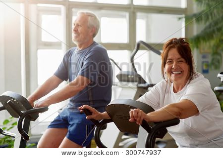Happy Senior Woman Working Out In Gym. Smiling Elderly Couple Exercising In Gym On Stationary Bicycl