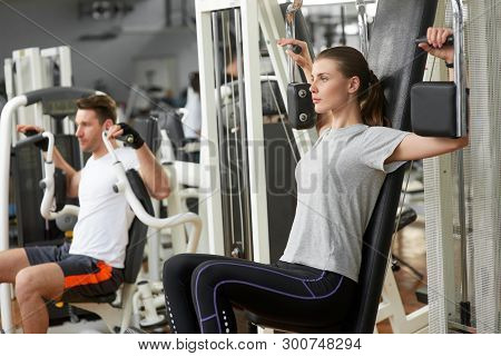 Young Athletic Woman Exercising In Gym. Man And Woman Training At Fitness Center. Attractive Female