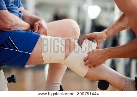 Senior Man With Bandage On Leg After Injury In Gym. Male Hands Fixed Elastic Bandage On Male Injured