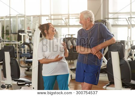 Two Happpy Senior People At Gym. Joyful Elderly Couple Laughing After A Sport Workout At Fitness Clu