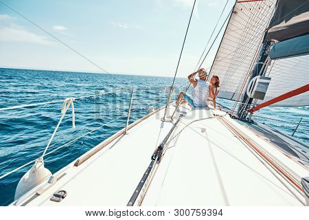 Young happy woman with man relaxing on sailboat deck on vacation