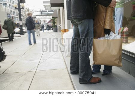 Low section of couple window shopping