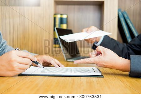 Hand of a businessman hands over a resignation letter final remuneration to executive boss on a wooden table to his boss Change of job, unemployment concept. poster