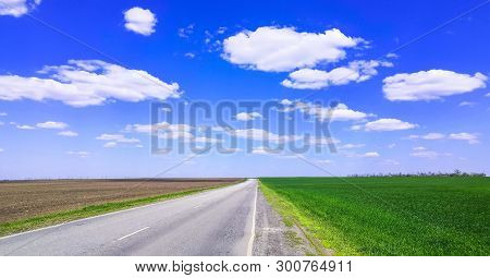 Empty Highway Through Green Grass Field Under White Clouds On Bright Blue Sky In Spring Summer Day.