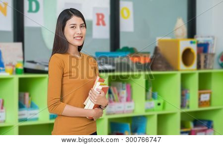 Teacher Holding Learning Look At Library In Kindergarten Preschool.education Concept.
