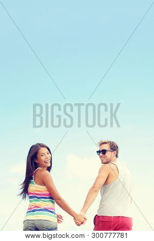 Happy young couple in love holding hands laughing on blue sky background with lots of copy space vertical crop. Interracial people, Caucasian man and multiracial Asian woman smiling.