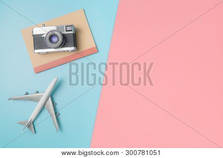 Camera And Notebook Tablet For Travel Concept On Blue Pink Background