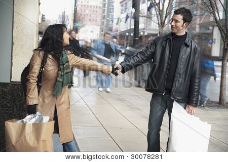 Couple holding hands on sidewalk