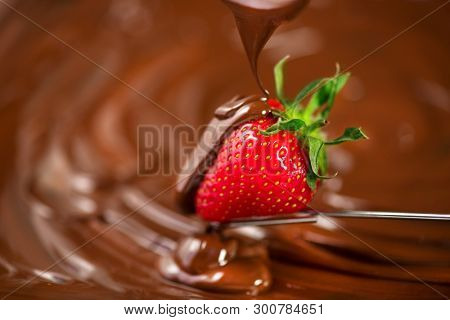 Strawberry in chocolate over swirl brown background. Melted Chocolate pouring on fresh ripe juicy strawberry close up. Dessert. Gourmet food. Fondue