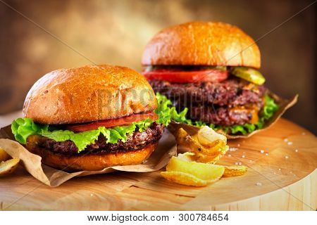 Hamburger and Double Cheeseburger with fries rotated on wooden table background. Cheeseburgers on fresh buns with succulent beef and fresh salad ingredients served with French Fries