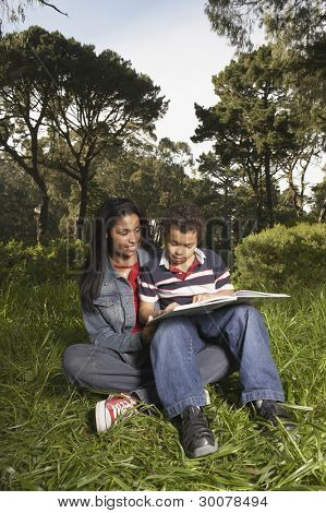 Mother and son reading in meadow