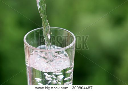 Pouring Clean Water Into Drinking Glass On Green Nature Background. Concept Of Health And Freshness,
