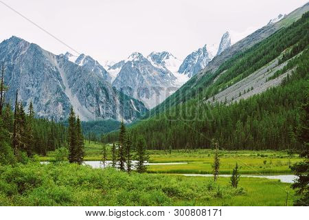 Mountain Creek Of Serpentine Shape In Valley Against Snowy Mountains. Water Stream In Brook Against