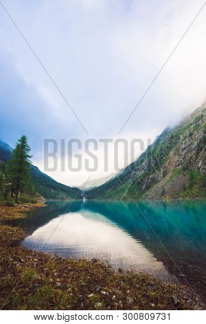 Amazing Mountain Lake In Overcast Weather. Mountains, Cloudy Sky And Morning Sunlight Reflected In C