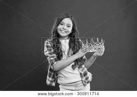 My biggest treasure. Kid hold golden crown symbol of princess. Childhood concept. Every girl dreaming to become princess. Girl cute baby hold crown while stand red background. Lady little princess. poster