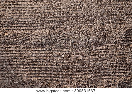 Preparation Of Land Before Planting. The Texture Of The Ground With Horizontal Grooves From The Rake