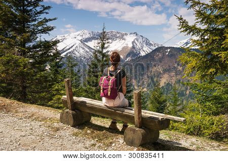 Girl Relaxing After Hike Looking To Mountain View. Traveler Sitting On Wooden Bench Enjoying Beautif