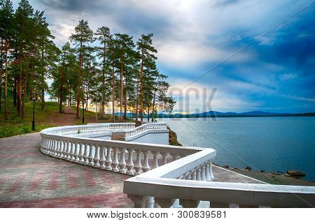 Summer sunset landscape - summer trees at the edge of the cliff and lake under cloudy dramatic sky. Colorful summer landscape evening scene