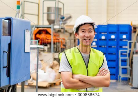 Front View Of Asian Factory Worker With Safety Hard Hat Posed Looking At Camera With Happy Smile In