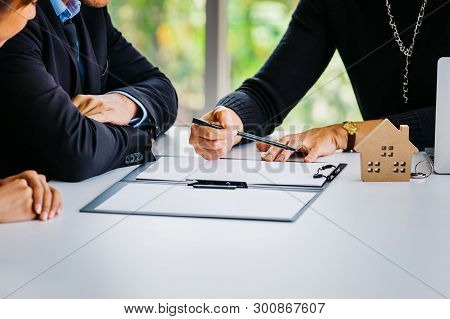 Close-up Of Married Couple Signing Contract Paper Alongside With Female Agent - Real Estate, Housing