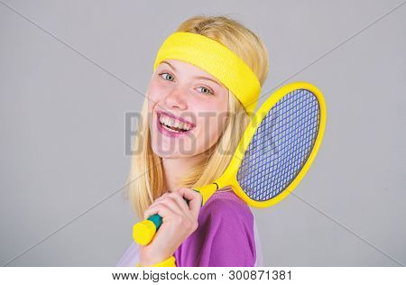 Girl adorable blonde play tennis. Sport for maintaining health. Athlete hold tennis racket in hand on grey background. Tennis club concept. Active leisure and hobby. Tennis sport and entertainment poster
