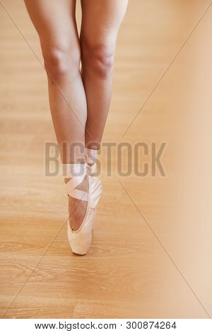 Close-up Of Unrecognizable Woman In Pointe Shoes Standing On Tiptoes While Performing Ballet At Rehe