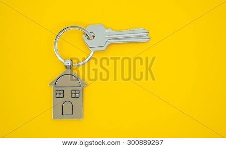 key chain with house symbol and keys on yellow background,Real estate concept