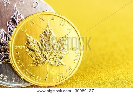 Closeup Of Silver And Golden Maple Leaf One Ounce Coins On Golden Background Placed On Left Side
