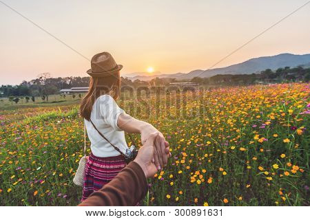 Young Woman Traveler Holding Man's Hand And Leading Him On Flowers Field, Couple Vacation Travel Con