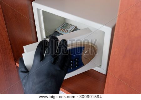 Close-up Of Hand A Thief In A Black Glove Opening A Safe With Dollars To Steal Them. Code Lock Prote