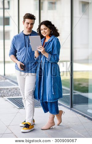 Young Cute Couple - A Boy And A Girl Standing Near A Glass Building. A Couple Have Fun Spending Time