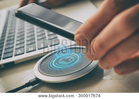 Smartphone in hand near a wireless charging pad, charger.