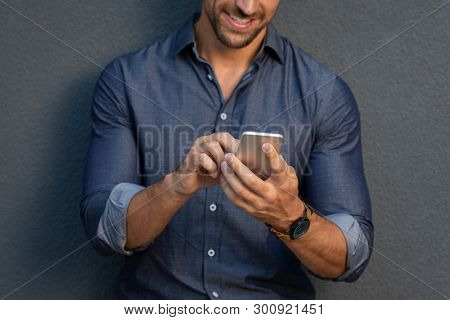 Closeup of a man using smartphone on gray wall. Businessman hand messaging with mobile phone isolated against grey background. Smiling handsome man in smart casual using cellphone app.