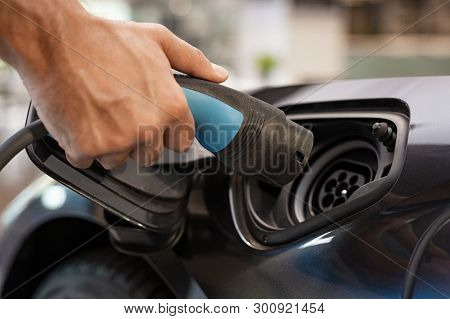 Closeup of man hand installing power cable supply for charging electric car. Man hand plugging in power cable to his car. Male hand grabbing electric charger device for charging battery.