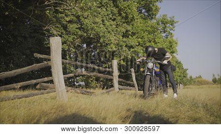 Motorcyclist Pulls A Broken Bike. Motorcyclist Rolls His Motorcycle. Motorcyclist Goes Near His Bike