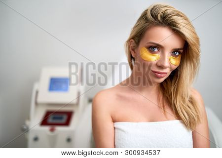Portrait Of Attractive Blonde Caucasian Woman With Golden Eye Patches Showing An Effect Of Perfect C