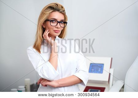 Smiling Confident Female Beautician Doctor In Lab Coat Standing In Her Office With Medical Hardware