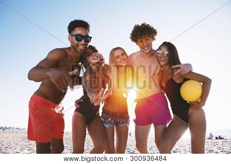 Group Of Friends Playing At Beach Volley At The Beach. Morning, Sunlight.