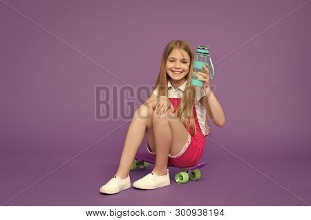 Staying Hydrated. Girl Happy Face Holds With Water Bottle While Sits Skateboard, Violet Background.