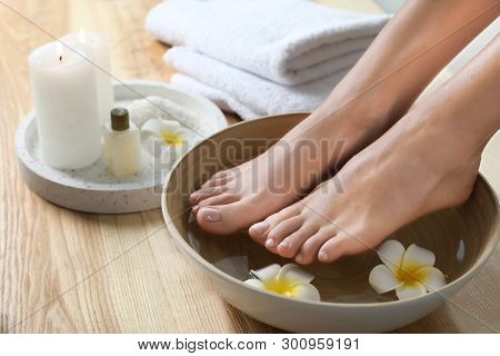 Closeup view of woman soaking her feet in dish with water and flowers on wooden floor. Spa treatment poster