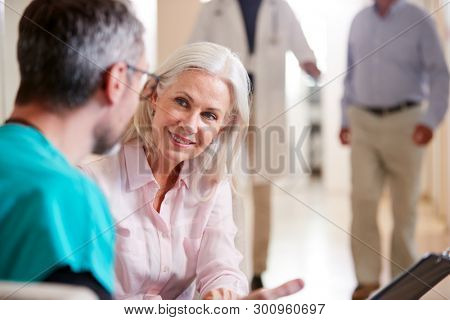 Doctor Welcoming To Senior Female Patient Being Admitted To Hospital