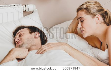 Copule in bed. Woman trying to wake him, in morning. They are waking up.