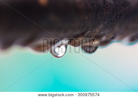 Closeup Of Water Droplets On A Rusty Iron Rod With Out Of Focus Colorful Background